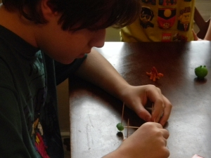 brown haired teenager constructing a cube with toothpicks and gumdrops