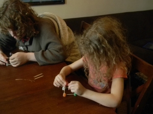two children, boy and a girl with curly hair, constructing geometric solids