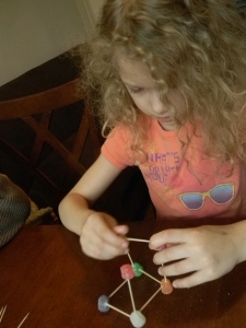 young girl constructing a cube